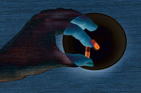Hand taking a pill in luminescent light photo