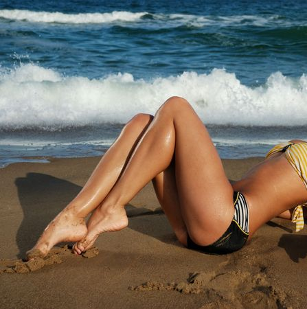 bare girl: tan legs on a beautiful tropical beach