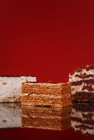 Appetizing cakes on dark red background photo