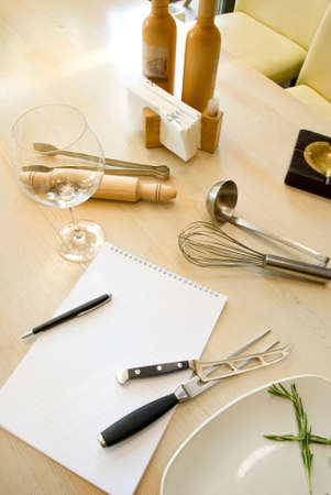 Utensils, notebook and glass of wine photo