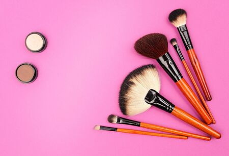Cosmetics and brushes for a make-up on a pink background photo