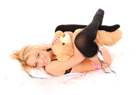 laying in bed smiling girl with a toy bear over white photo