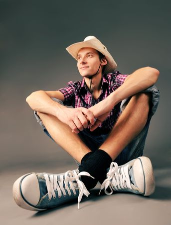young smiling guy in sneakers and hat sitting against green background photo