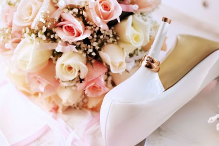 wedding bouquet: Wedding background from rings, bouquet and white shoes bridge Stock Photo
