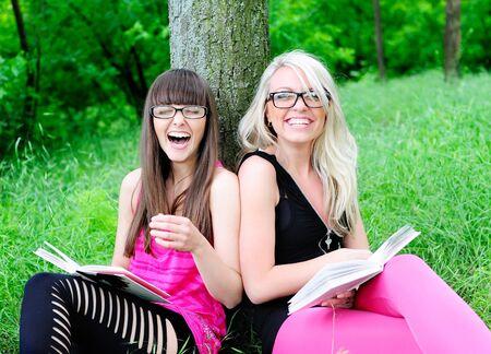 chicas divirtiendose: dos ni�as de estudiante bastante divertido leer los libros Foto de archivo