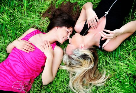 two young pretty girls laying in grass photo