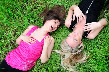 two young pretty smiling girls laying in grass  photo