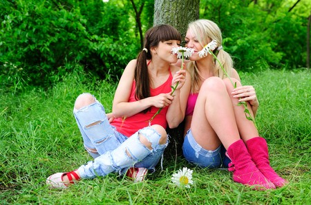friendship women: two young pretty girls with flowers sitting on a grass  Stock Photo