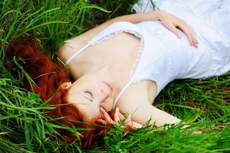 Cute young redhead female lying on grass field at the park  photo