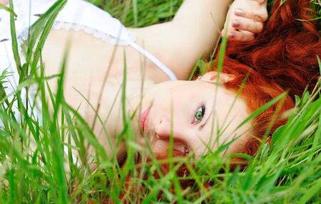 redhead: Cute young redhead female lying on grass field at the park