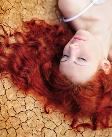 Młoda kobieta Beauutiful z Rude włosy na ziemi suszone w górę