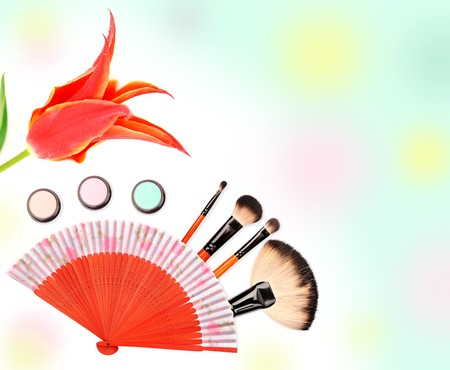 Cosmetics and brushes for a make-up on a colorful background photo