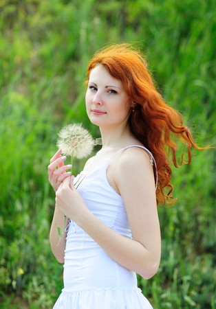 redhead: Cute young redhead female with big dandelion in her hands Stock Photo