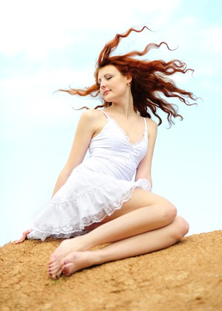 Cute young smiling female with red hair fluttering in the wind photo