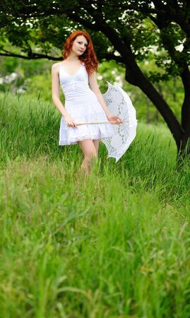 Cute young redhead female standing on grass field at the park with umbrella photo
