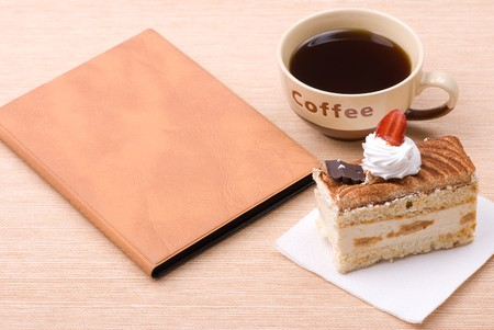 Biscuit cake with cup of coffee and book photo