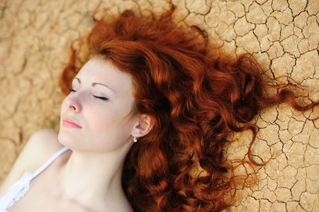 Beauutiful young woman with red hair on the dried up ground photo