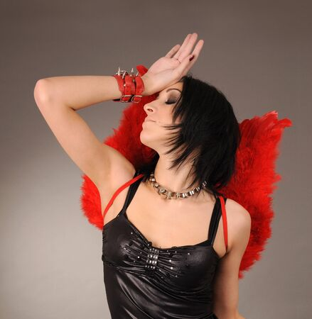 Attractive girl with angelic wings and handcuffs,studio shot photo