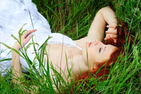 Cute young redhead female sleeping on grass field at the park  photo