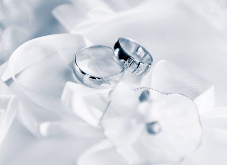 faithfulness: Wedding rings on a satiny fabric with bow