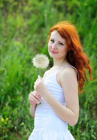 Cute young redhead female with big dandelion in her hands photo