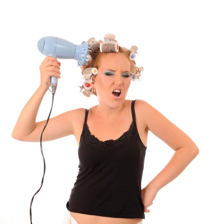 Bored attractive housewife with a hair dryer Stock Photo - 8110588