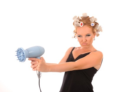 Bored attractive housewife shoot a hair dryer Stock Photo - 8110585
