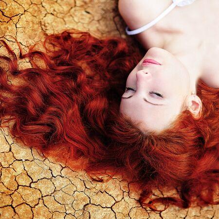 pelo rojo: Beauutiful joven mujer con cabello rojo sobre el terreno seco hasta  Foto de archivo