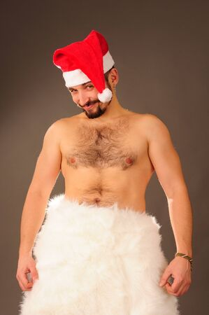 Young happy man with naked torso in Santa hat. photo