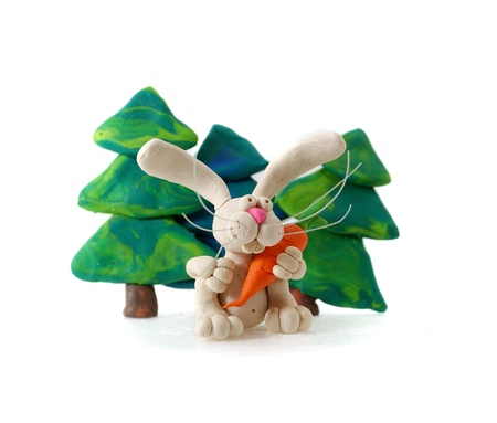 zanahoria de caricatura: Conejo de plastilina con zanahoria contra abetos. Foto de archivo