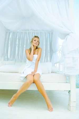 Young sexual attractive blond woman dressed in a towel sitting on a lounger photo