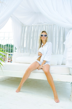 Young sexual attractive blond woman dressed in white sitting on a lounger on sea beach.  photo