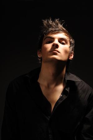 poses de modelos: Retrato de hombre joven valiente sobre fondo negro.