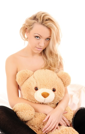 Portrait of sitting beautiful girl with a toy bear over white. photo