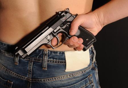 Man hiding behind a gun on black background. Stock Photo - 8486541
