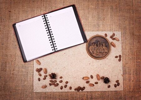 sacking: open notebook with nature elements and medallion on a sacking