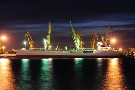 View on seaport with cranes and cargo ship at the night. photo