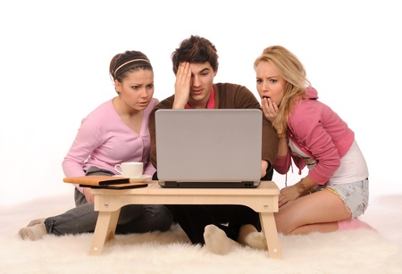 Group of frightened young people having fun with laptop on white background. Stock Photo - 8669040
