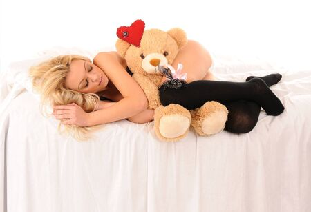 picture of lying on a bed beautiful girl with a toy bear over white photo