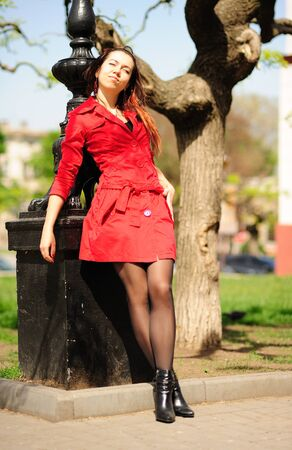 Young smiling girl in a red coat is basking in the sun. Stock Photo - 8732864