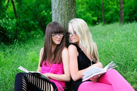 two pretty student girls reading books in park Stock Photo - 8732871