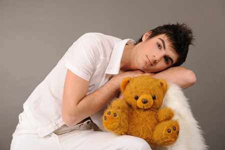 Attractive young man with toy bear on gray background photo