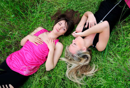 Two young pretty girls laying in grass. photo