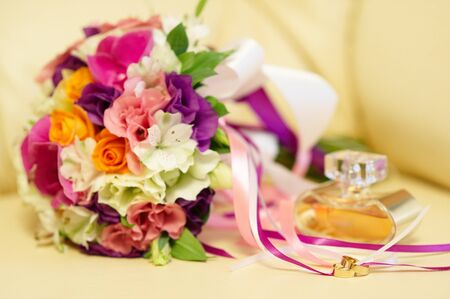 Wedding rings, bouquet and perfume, soft focus. photo