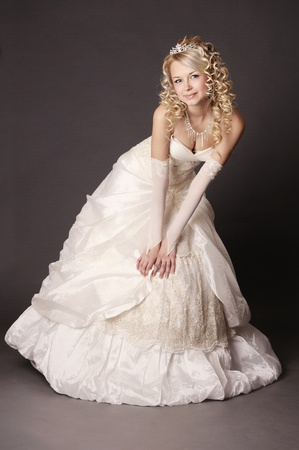 Beautiful woman dressed as a bride over gray background. photo