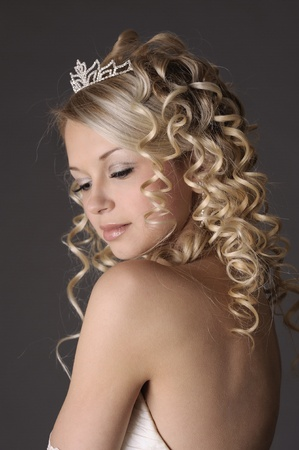 Portrait of a beautiful woman dressed as a bride over gray background. photo
