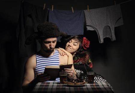 Fun loving couple, reading a book, retro rural imitation. Stock Photo - 9314799