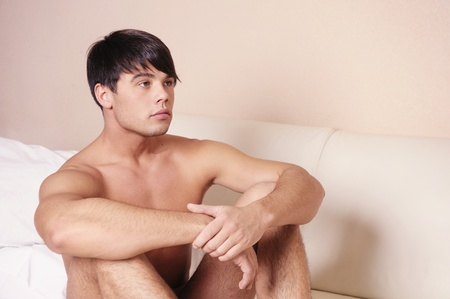 males only: Young sexy man sitting on a bed.