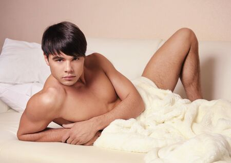 only young men: Young sexy man lying on a bed. Stock Photo
