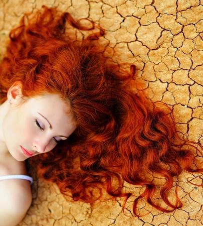 pelo rojo: Joven y bella mujer con cabello rojo sobre el terreno seco hasta.